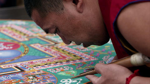 Hand held shot of a man adding sand to a sand mandala Footage