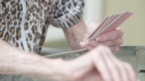 Tight shot of an elderly lady playing cards Footage