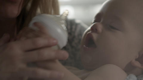 Tight shot of a mother bottle feeding her baby Footage