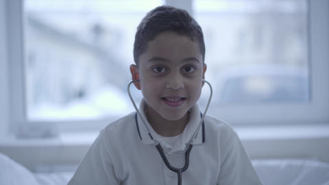 Portrait of cute small boy with stethoscope in his ears looking in camera Footage