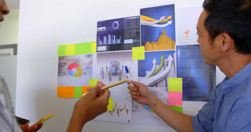 Multi-ethnic business colleagues discussing over graphs and sticky notes in modern office 4k Live Action