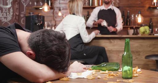 Drunk custumer sleeps on a wooden dirty table Footage