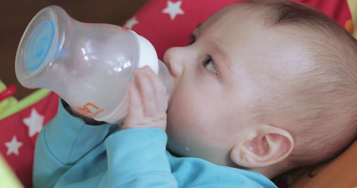 Child learns to drink from a bottle Footage