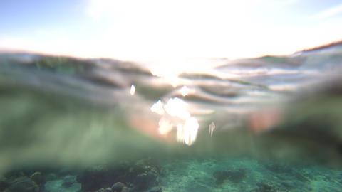 4k - beautiful underwater shot with sunlight sunbeams on the surface of water Footage