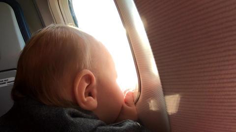 Little blonde boy looks in the window of airplane furing flight Archivo