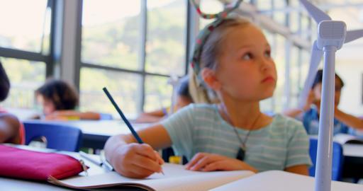 Caucasian schoolgirl studying at desk in classroom 4k Live Action