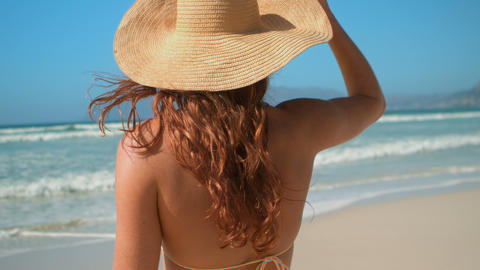 Young Caucasian woman in bikini and hat standing on beach in the sunshine 4k Live Action