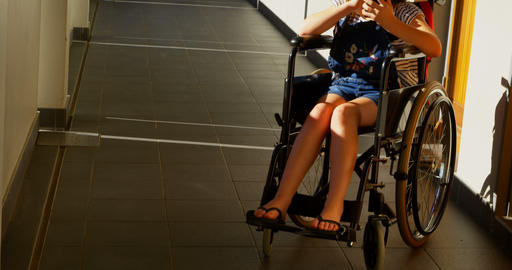 Disabled schoolgirl using mobile phone in the corridor 4k Live Action