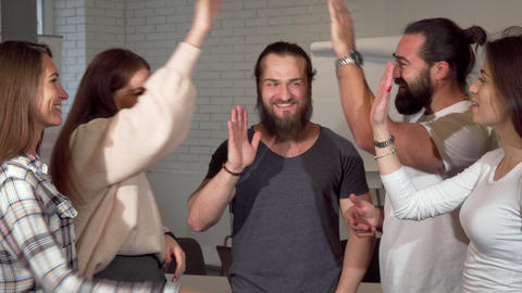 Group of entrepreneurs celebrating success, high fiving each other Footage