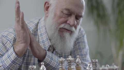 Portrait of mature man thinking which chess piece to make a move. Two people Live Action