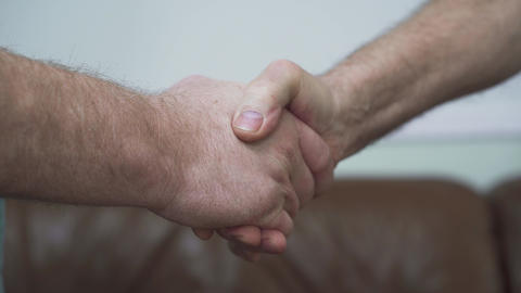 Two senior mature men shaking hands close up. Friendship of the old friends Live Action