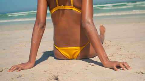 Young African American woman in yellow bikini relaxing on beach in the sunshine 4k Live Action