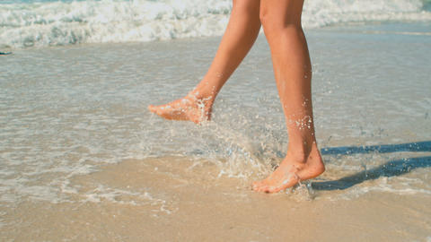 Woman playing in waves on beach in the sunshine 4k Live Action