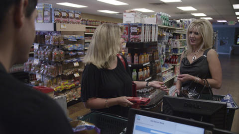 Two women at the grocery store register, one offers to pay for the other Footage