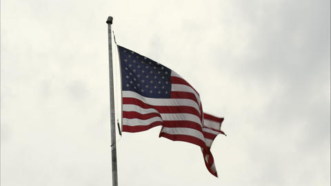 United States' flag waving in the wind with partially cloudy sky Footage