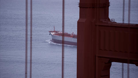 Tight shot of a shipping vessel seen through some of the Golden Gate structure Footage