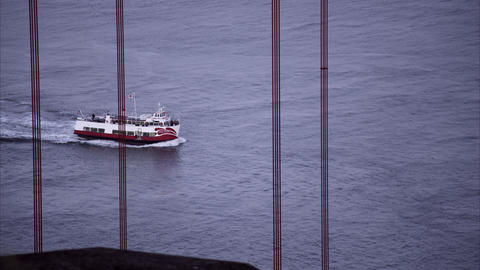 Tight shot of a ferry as seen through the support structure of the Golden Gate B Footage