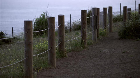 Static shot of a fence along a pathway with water in the background Footage