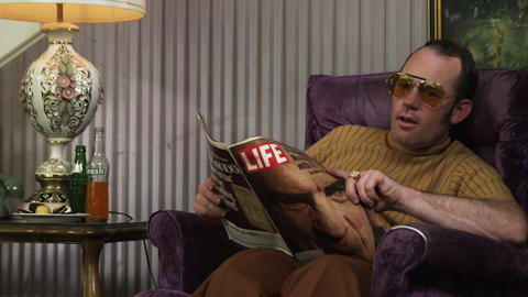 Retro style shot of a dad reading a magazine and talking to people Footage