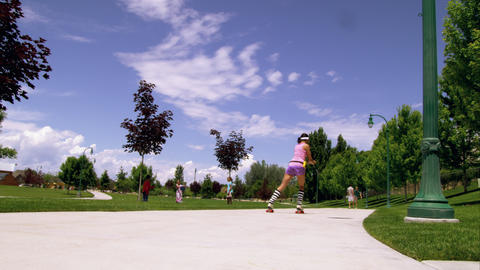 Woman dressed in 80's athletic clothing roller skating in the park Footage
