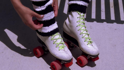 Tight shot of a woman adjusting leg warmers on her roller skates Footage