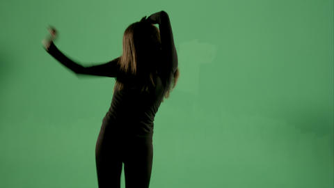 Backlit woman on green screen dancing Footage