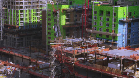High rise construction site with crane lifting materials Footage