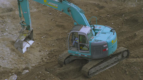 Shot from above of a trackhoe moving concrete chunks Footage