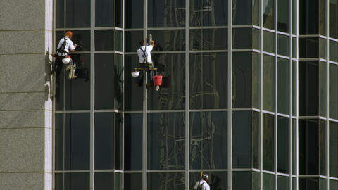 Tight shot of three window washers on lines washing a highrise building Footage