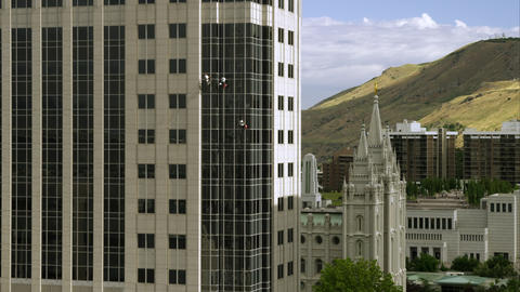 Three window washers on lines washing a highrise building. LDS Salt Lake Temple  Footage