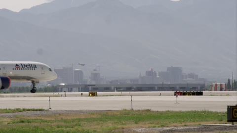 Commercial airliner trucking on a runway. With Salt Lake City in the background Footage
