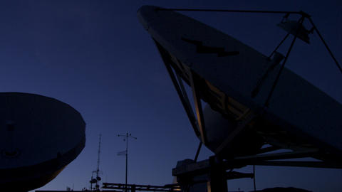 Panning dusk shot of silhouetted satellite dishes against the sky Footage