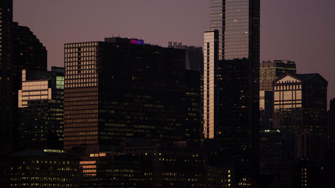 Tight panning shot of nearly silhouetted buildings in Chicago at dusk Footage