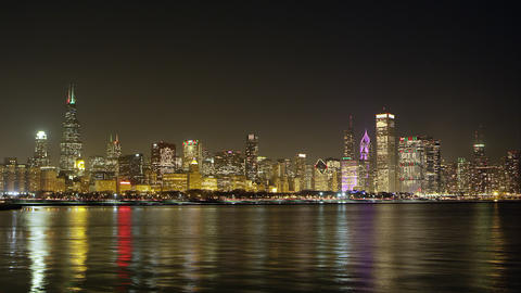 Night timelapse of Chicago from across the water. Airplanes visible Footage