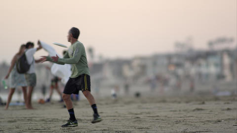 Man Tossing Frisbee On California Beach Footage