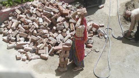 Women Laborer carrying bricks on head Live Action