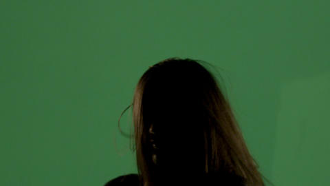 Tight shot of a near silhouetted woman on green screen dancing Footage