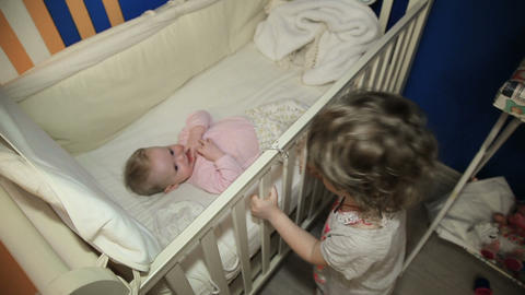 Girl stands near the bed with their baby sister Footage