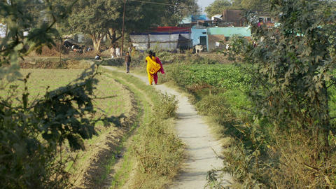 Two women walk down dirt path in bright colored saris Footage