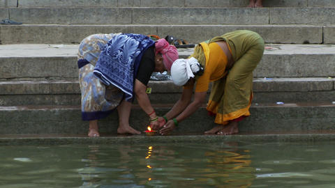 Two women lighting floating candles Live Action