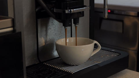Black coffee streaming in a cup from a coffee mashine GIF