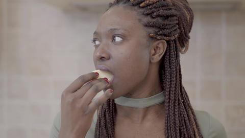 Portrait of confident african american young smiling woman biting tasty slice of Footage