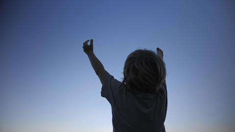 Child silhouette raising hands up in the air on blue sky background Footage