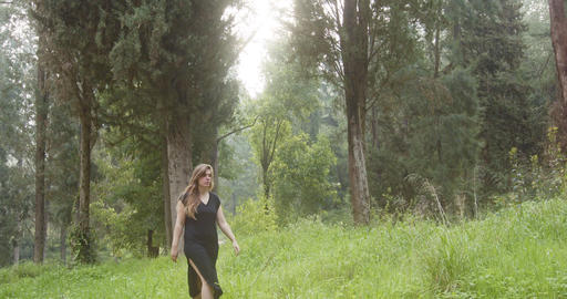 Young beautiful woman with a black dress walking in a green forest Live Action