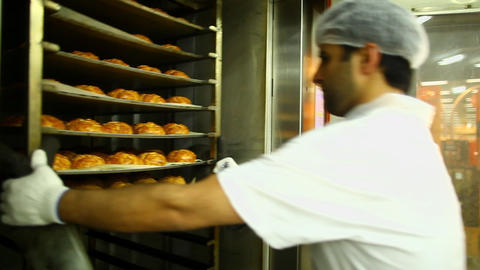 Baker pulls out fresh bread from the oven Stock Video Footage