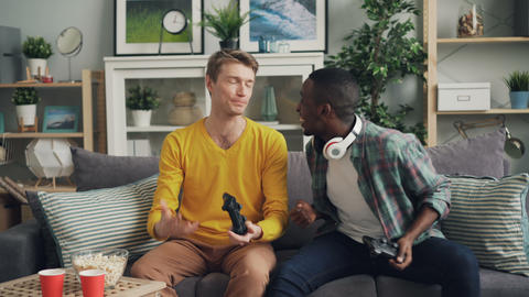Cheerful guys are playing video game at home expressing emotions and relaxing on Footage