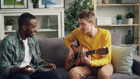 Happy guys African American and Caucasian are learning to play the guitar using Footage