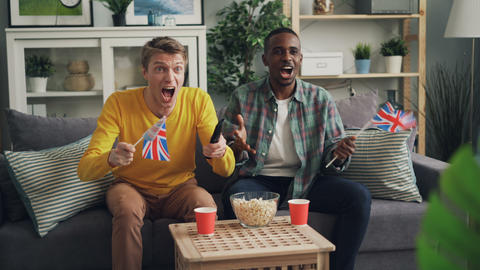 Excited young people are supporting British team watching sports game on TV and Footage