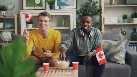 Handsome guys sports fans are watching competition on TV holding Canadian flags Footage