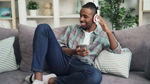 Good-looking African American man in casual clothing is listening to music in Footage